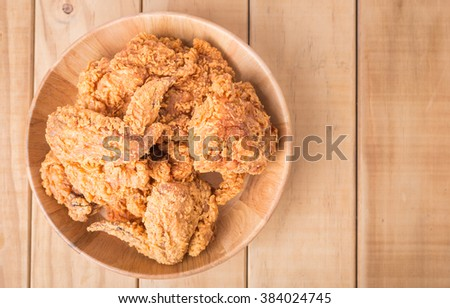Top view fried chicken in wooden plate on wooden table - stock photo
