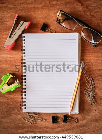 Top view from blank notepad workspace with pencil, glasses, paperclip, strips on wooden table background. Copy space for text - stock photo
