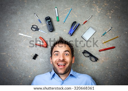 Top view funny photo of businessman with beard wearing shirt. Businessman cheerfully smiling and lying on floor full of office supplies - stock photo