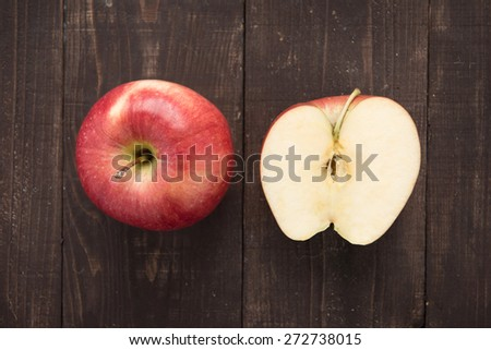 Top view half fresh ripe red apples on wooden background. - stock photo
