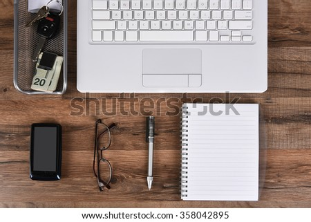 Top view home office business desk with laptop computer, cell phone, note pad, pen, glasses, money clip, car keys on a dark wood desk. - stock photo