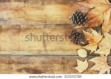 top view image of autumn leaves and pine cones over wooden textured background  - stock photo