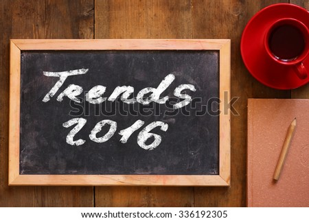 top view image of chalkboard with the text 2016 trends' next to cup of coffee and notebook - stock photo