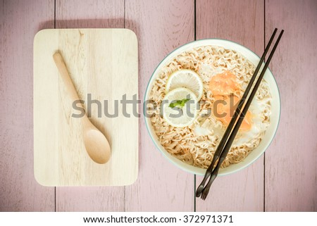 Top view image of Chinese noodle in bowl on top of rustic wood.