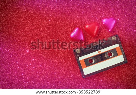 top view image of colorful heart shape chocolates and audio cassette on red glitter background. valentine's day celebration concept