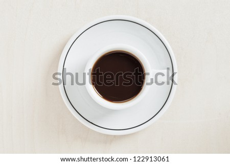 Top view image of cup of black coffee in a plate isolated on
