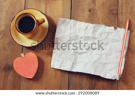 top view image of empty crumpled paper, coffee cup and heart shape over wooden table  - stock photo