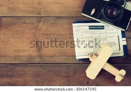 top view image of flying ticket wooden airplane and vintage camera over wooden table. retro filtered image  - stock photo
