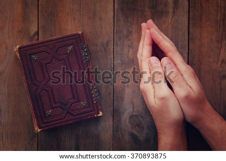 top view image of mans hands folded in prayer next to prayer book. concept for religion, spirituality and faith  - stock photo