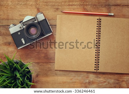 top view image of open blank notebook and old camera. retro filtered  - stock photo