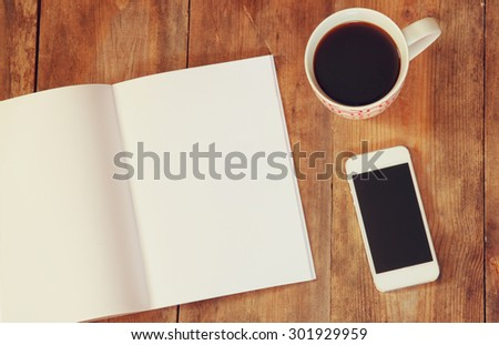 top view image of open notebook with blank pages next to cup of coffee and smartphone on wooden table. ready for adding text or mockup  - stock photo