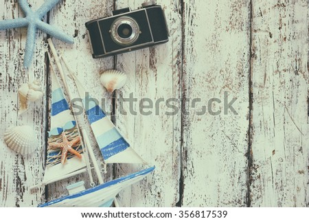 top view image of photo camera, wood boat, sea shells and star fish over wooden table  - stock photo