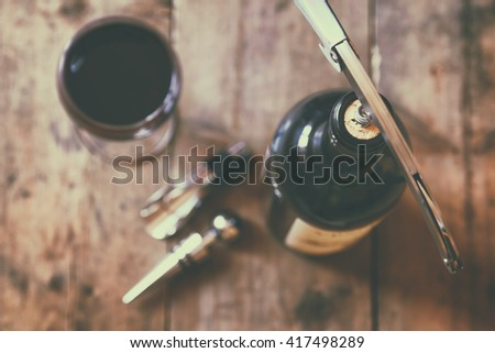 top view image of red wine bottle and corkscrew over wooden table. retro style image selective focus. - stock photo