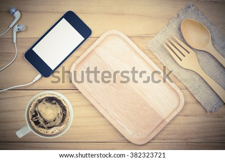 top view image of smart phone with coffee cup and kitchen tool on wooden table,vintage tone,still life - stock photo