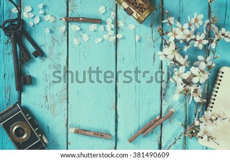 top view image of spring white cherry blossoms tree, blank notebook, old camera on blue wooden table. vintage filtered and toned - stock photo