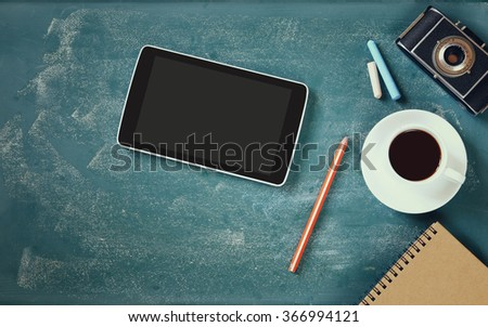 top view image of tablet, cup of coffee and photo camera over blackboard background  - stock photo