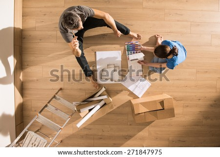 top view, looking at the camera a young couple sitting on the floor of their new home, there are blueprints to help them to think about their new interior decoration - stock photo