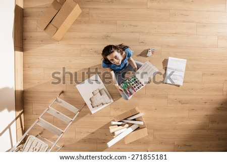 top view, looking at the camera a young woman sitting on the floor of her new home, there are blueprints and samples colors to help her to think about her new interior decoration - stock photo