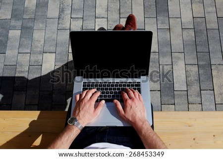 Top view male hands using notebook outdoors in urban setting while typing on keyboard, businessman freelancer working on computer while sitting on city park bench, tourist working on laptop  - stock photo