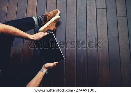 Top view male student using touch pad while sitting on wooden floor,modern successful businessman working on his digital tablet with big copy space,hipster man's hands browsing with touchscreen device - stock photo