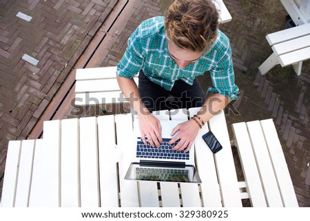 Top view man working with laptop outside - stock photo