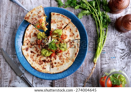 top view mexican cuisine quesadilla served at blue plate with guacamole, salsa and jalapenos - stock photo