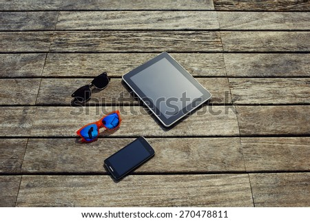 Top view mock up presentation with blank screen digital tablet, smart phone and couple of sunglasses lying on the wooden texture, vacation holidays or recreation time concept, objects on wooden pier - stock photo
