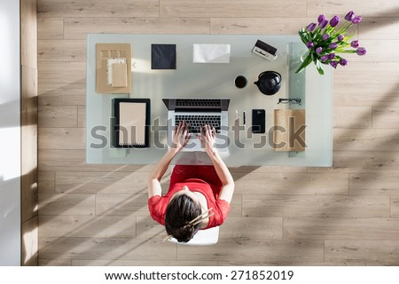 top view, Modern businesswoman sitting at glass desk and working on her laptop, her table is perfectly tidy, the sun casts graphics shadows on the wood floor - stock photo