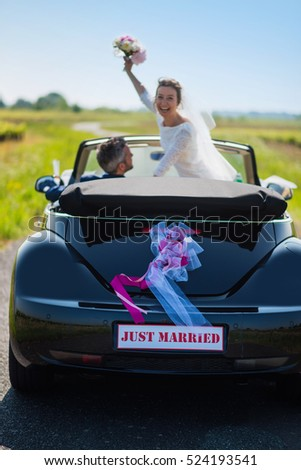 Top view. newlyweds going on honeymoon by convertible car on a country road.The shape of the car has been modified so as not to be recognizable.
