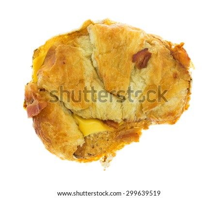 Top view of a bacon egg and cheese croissant breakfast sandwich with a bit of bacon on the crust isolated on a white background. - stock photo