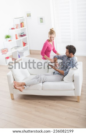 top view of a beautiful couple relaxing on a white sofa and using a digital tablet - stock photo