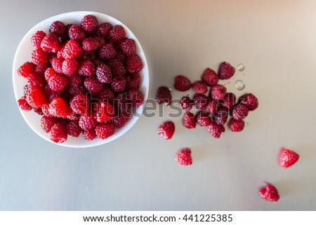 Top view of a beautiful selection of freshly picked ripe red raspberries in the white bowl on a metal background, selective focus, shallow depth of field - stock photo
