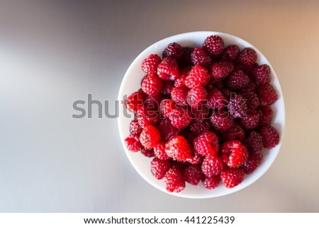 Top view of a beautiful selection of freshly picked ripe red raspberries in the white bowl on a metal background - stock photo