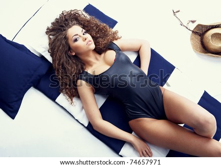 Top view of a beautiful young woman lying on beach - stock photo