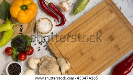 Top view of a blank wooden serving board with yellow bell pepper, red chili peppers, tomatoes, basil, mushrooms, courgettes, black peppercorns and salt on a white marble background with copy space. - stock photo