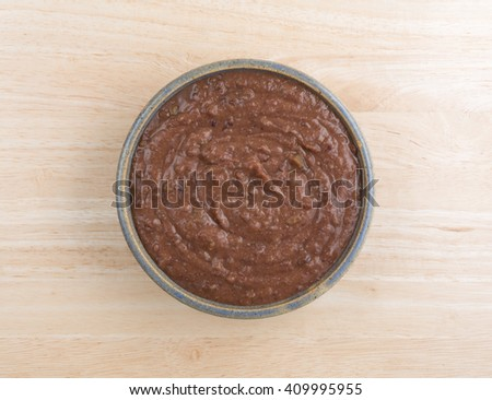 Top view of a bowl filled with black bean dip atop a wood table top.