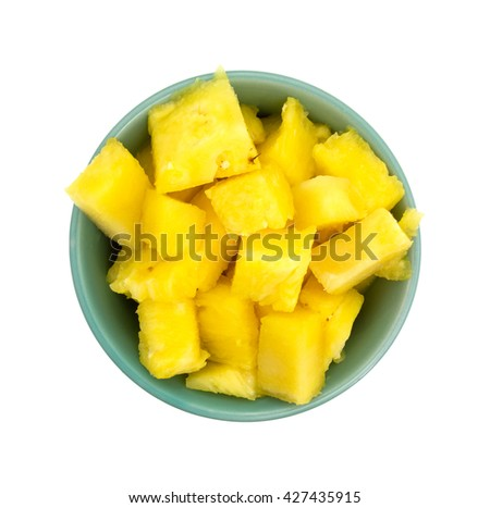 Top view of a bowl filled with freshly cut pineapple isolated on a white background.