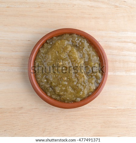 Top view of a bowl of culantro cooking sauce on a wood table.