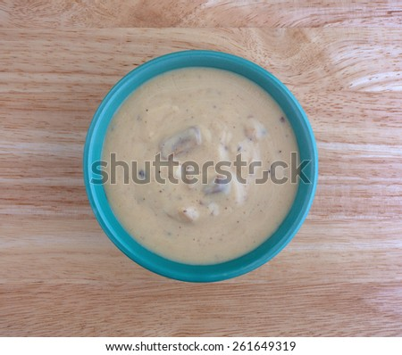 Top view of a bowl of portabella mushroom soup on a wood table top. - stock photo