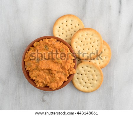 Top view of a bowl of spicy chicken salad with butter crackers to the side atop a marble cutting board. - stock photo