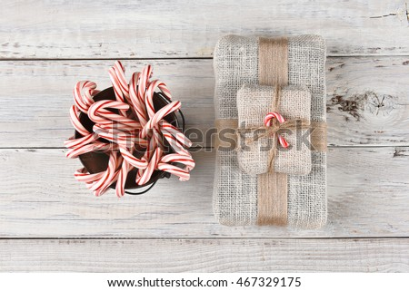 Top view of a bucket filled with holiday candy canes and a burlap fabric wrapped Christmas present.
