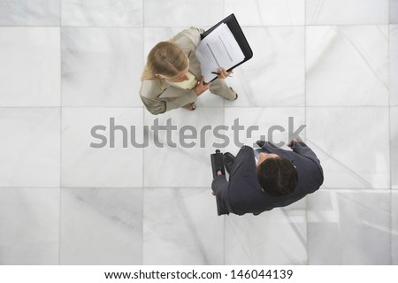 Top view of a businessman and woman conversing in office lobby - stock photo