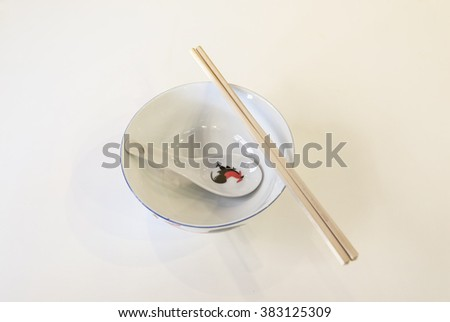 Top view of a ceramic spoon, bowl and a pair of wooden chopstick traditionally used in eating Chinese food.   - stock photo