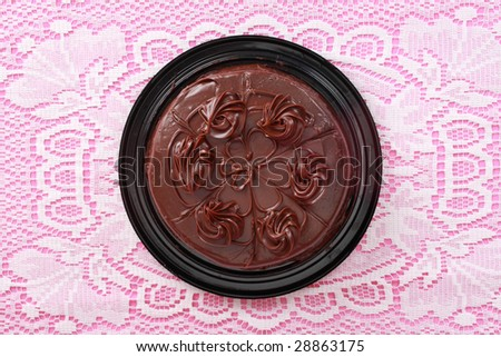 top view of a chocolate cake over a pink and white tablecloth - stock photo