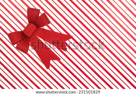 Top view of a Christmas red and white striped box with a large red ribbon. - stock photo