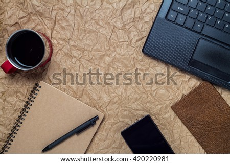 top view of a computer, laptop, cake, cup of coffee, notebook, smartphone, and office workspace vintage style