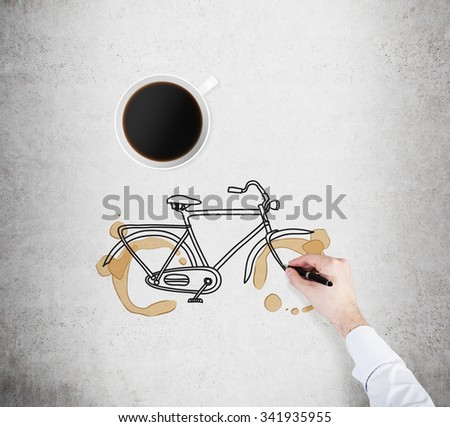 Top view of a cup of coffee and a drawing process of a bicycle on the concrete surface. A hand in formal white shirt with a pen. - stock photo