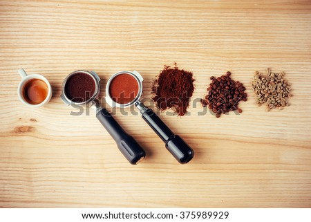 Top view of a cup of coffee and three different varieties of coffee beans. - stock photo