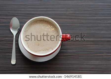 Top view of a cup of coffee on a wooden table with copy space - stock photo