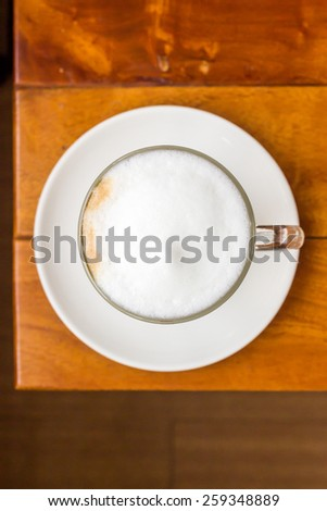 Top view of a cup of coffee on wooden table - stock photo